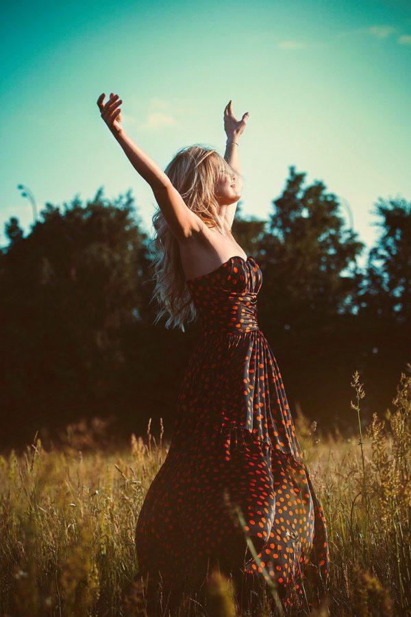 Femme libérée les bras en l'air au coeur d'un champ