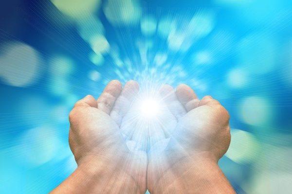 Main jointe qui fait émerger de la lumière