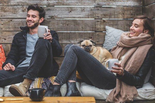 Femme, homme et chien heureux dans une cabane en buvant une boisson chaude