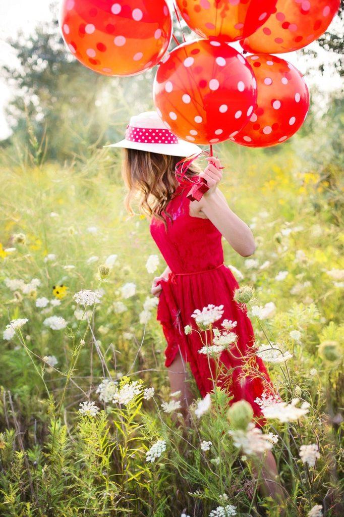 Femme habillée en rouge dans un champ avec des ballons rouges