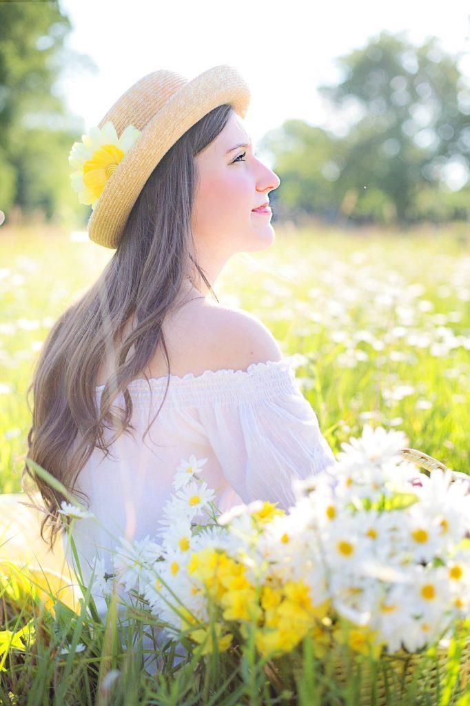 Femme dans un champ de fleur qui regarde l'horizon